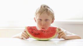 Il ragazzino mangia la grande fetta rossa di anguria stock footage