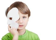 Il ragazzino nasconde la metà del fronte dietro la mascherina Fotografie Stock