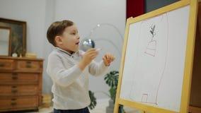 Il ragazzino nel salone della casa attinge il bordo con gli indicatori un disegno del ` s del bambino Istruzione prescolastica stock footage
