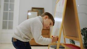 Il ragazzino nel salone della casa attinge il bordo con gli indicatori un disegno del ` s del bambino Istruzione prescolastica video d archivio