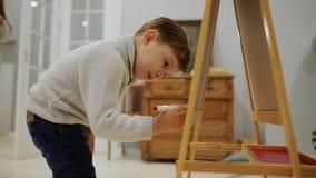Il ragazzino nel salone della casa attinge il bordo con gli indicatori un disegno del ` s del bambino Istruzione prescolastica archivi video