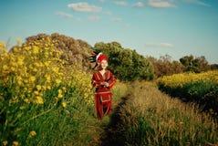 Il ragazzino nell'indiano rosso del vestito funziona sulla pista nel campo con alta erba Immagine Stock