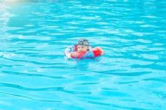 Il ragazzino nuota, bambino allegro che salta nello stagno nel cerchio, piscina all'aperto, Fotografie Stock