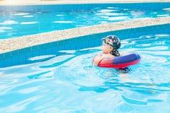 Il ragazzino nuota, bambino allegro che salta nello stagno nel cerchio, piscina all'aperto, Immagine Stock Libera da Diritti