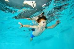 Il ragazzino nuota underwater e sale come un uccello, spandente le sue mani su un fondo blu Immagini Stock