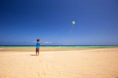 Il ragazzino pilota un aquilone su una spiaggia, Fuerteventura, isole Canarie, Spagna fotografia stock