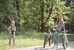 Il ragazzino prende le immagini di sua madre mentre cammina nel parco immagini stock