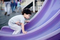 Il ragazzino scala sul modo dell'inverso dello scorrevole Immagini Stock Libere da Diritti