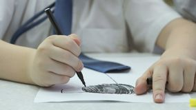 Il ragazzino sconosciuto dipinge le immagini con la penna a feltro stock footage