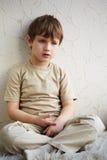 Il ragazzino si siede da solo sulla coperta bianca fleecy immagine stock libera da diritti