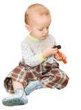 Il ragazzino si siede e considera un giocattolo martello di plastica L'isolante Fotografie Stock Libere da Diritti
