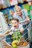 Il ragazzino si siede nel carrello di acquisto con l'anguria Fotografia Stock