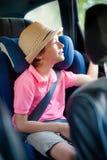 Il ragazzino si siede nel sedile della sicurezza immagine stock