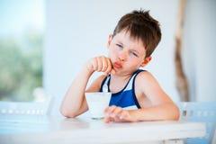 Il ragazzino sorridente rifiuta di mangiare il yogurt delizioso Immagini Stock Libere da Diritti