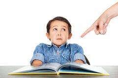 Il ragazzino spaventato esamina un dito quei punti a compito Fotografia Stock