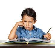 Il ragazzino spaventato esamina un dito quei punti a compito Fotografia Stock Libera da Diritti