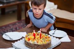 Il ragazzino spegne le candele sulla torta di compleanno Immagini Stock