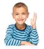 Il ragazzino sta aumentando la sua mano su Immagini Stock