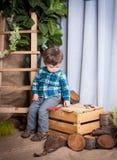 Il ragazzino sta giocando con gli strumenti di un carpentiere Immagini Stock