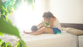 Il ragazzino sta giocando con sua madre sul divertimento di risata del letto video d archivio