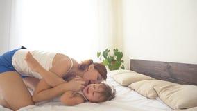 Il ragazzino sta giocando con sua madre sul divertimento di risata del letto stock footage