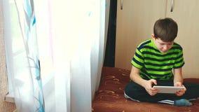 Il ragazzino sta giocando sulla compressa che si trova sul letto Internet sociale teenager di media del ragazzo su una compressa  archivi video