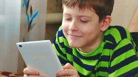 Il ragazzino sta giocando sulla compressa che si trova sul letto Internet sociale teenager di media del ragazzo su una compressa  stock footage