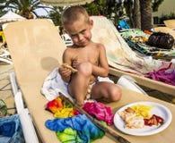 Il ragazzino sta sedendosi su una sedia di salotto con un piatto di alimento immagine stock