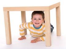 Il ragazzino sta sedendosi sulla tavola Fotografie Stock Libere da Diritti