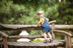 Il ragazzino sta stando sul banco fuori Fotografie Stock Libere da Diritti