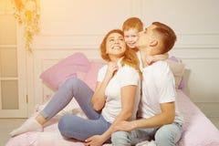 Il ragazzino sta stringendo a s? i suoi genitori che si siedono sul letto fotografia stock
