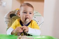 Il ragazzino sta tenendo una forcella e si mangia Immagine Stock