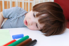 Il ragazzino stanco con feltro rinchiude il resto la sua testa su una tavola Fotografia Stock Libera da Diritti