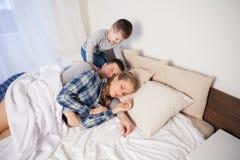 Il ragazzino sveglia di mattina, parents immagini stock libere da diritti