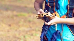 Il ragazzino sveglio in camicia blu ed il casco che si divertono all'avventura parcheggiano, tenenti le corde e prepering per sca immagine stock libera da diritti