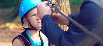 Il ragazzino sveglio in camicia blu ed il casco che si divertono all'avventura parcheggiano, tenenti le corde e prepering per sca immagini stock