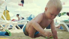 Il ragazzino sveglio che gioca i giocattoli con la sabbia alla spiaggia del mare OS del bambino sulla vacanza di estate alla spia video d archivio
