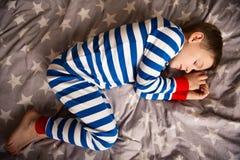 Il ragazzino sveglio dorme nei pajames sul letto Fokus qui sopra Fotografie Stock Libere da Diritti