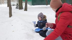 Il ragazzino sveglio e la giovane madre giocano nell'inverno con neve nel parco Rivestimento blu e rosso del ` s del bambino alla stock footage