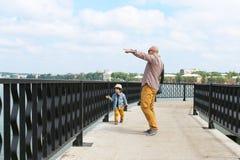 Il ragazzino sveglio ed suo padre camminano nell'estate immagine stock libera da diritti