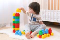 Il ragazzino sveglio gioca i blocchi di plastica Immagini Stock