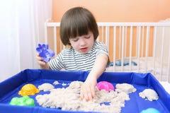 Il ragazzino sveglio gioca la sabbia cinetica a casa Fotografia Stock
