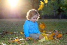 Il ragazzino sveglio sta giocando con i fogli in autunno fotografia stock libera da diritti