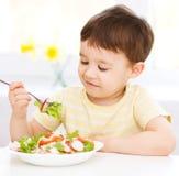 Il ragazzino sveglio sta mangiando l'insalata di verdure Immagine Stock