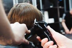 Il ragazzino sveglio sta ottenendo il taglio di capelli dal parrucchiere al parrucchiere immagini stock libere da diritti