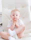 Il ragazzino sveglio sta sedendosi sulla sedia bianca Immagine Stock Libera da Diritti
