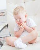 Il ragazzino sveglio sta sedendosi sulla sedia bianca Fotografia Stock Libera da Diritti