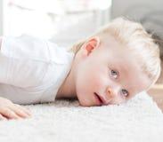 Il ragazzino sveglio sta trovandosi sul tappeto Immagini Stock Libere da Diritti