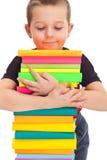 Il ragazzino tiene una pila di libri immagine stock libera da diritti
