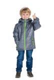Il ragazzino in un cappotto tiene il suo pollice su immagini stock